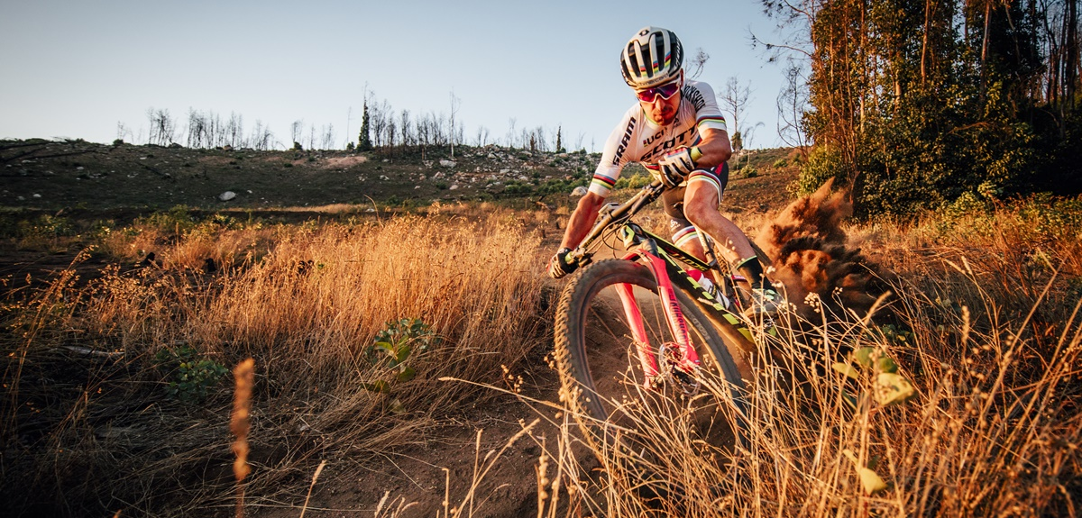 Nino Schurter: Taking a turn on a dry dirt trail.